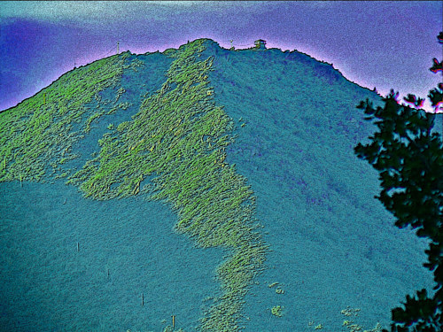 A manipulated photograph of a grassy mountain