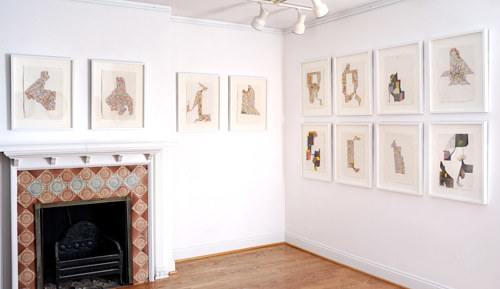 An installtion view of several small framed drawings