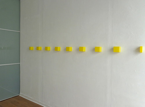 A series of yellow cubes adhered to a gallery wall