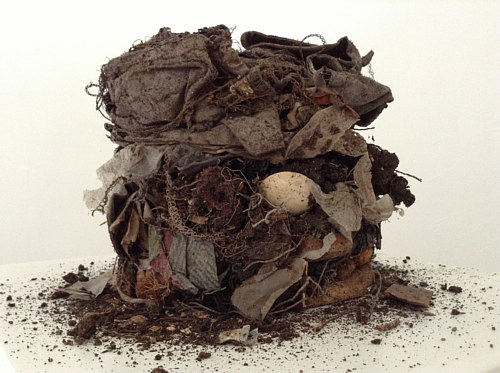 A sculpture made from soil and various found materials