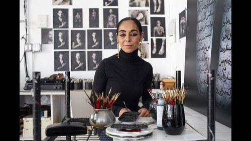 A photo of Shirin Neshat at work in her studio