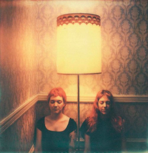 A polaroid photo of two figures sitting under a lamp