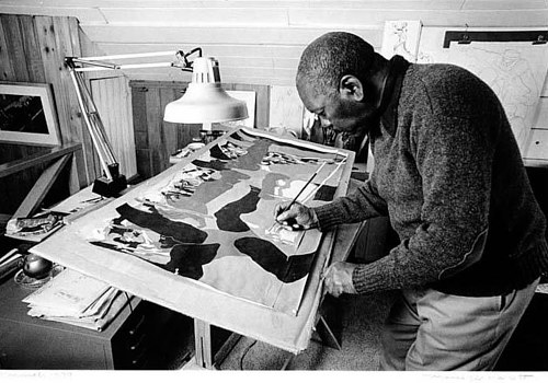 A photo of Jacob Lawrence at work in his studio