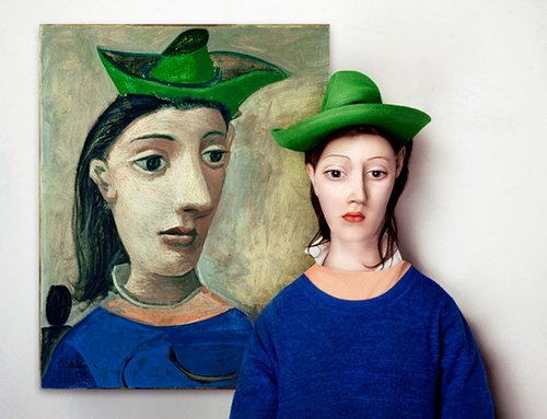 Woman with green hat next to painting of woman with green hat