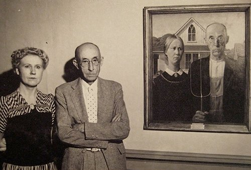 Man and woman standing next to painting of themselves