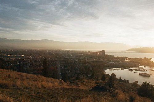 landscape photograph taken from a hillside overlooking the city with the sun's glare in the lens