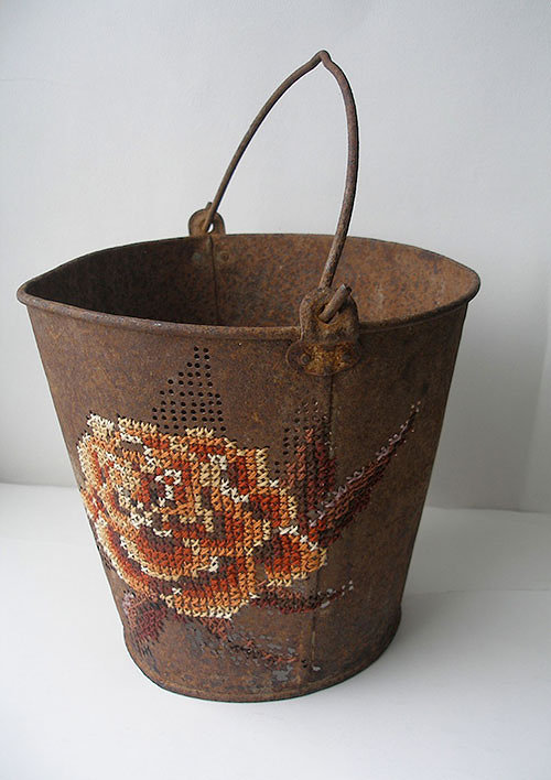 Photo of rusty pail with embroidery