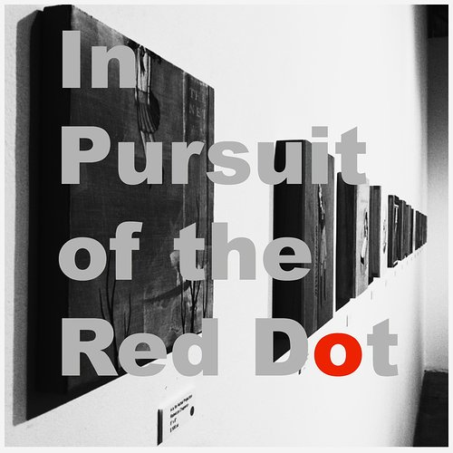 photograph of art with text overlay that says in pursuit of the red dot