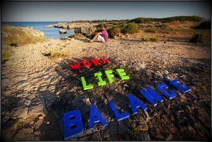 letters on a beach that says work life balance