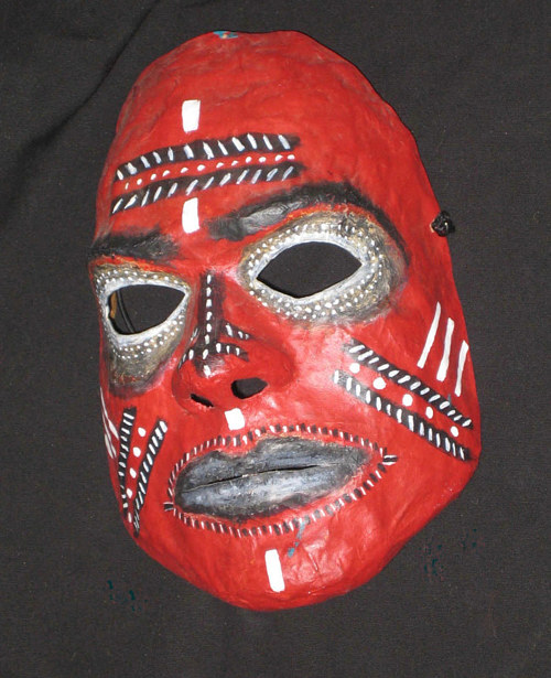 A handmade mask painted in bright red with patterning