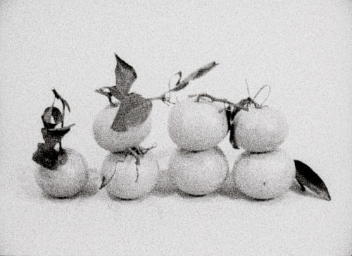 A film still featuring stacked mandarin oranges in black and white