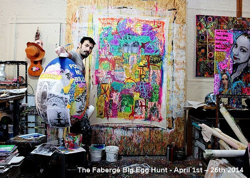 Artist in artist studio with giant egg and colorful paintings