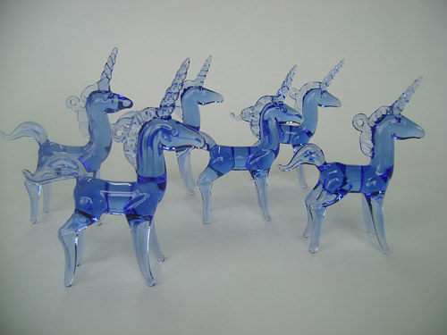 A photo of a set of blue sculpted glass unicorns