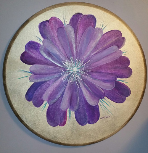 A painting of a purple flower on a round canvas