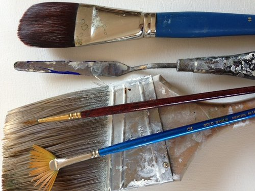 Four dirty paint brushes and a palette knife
