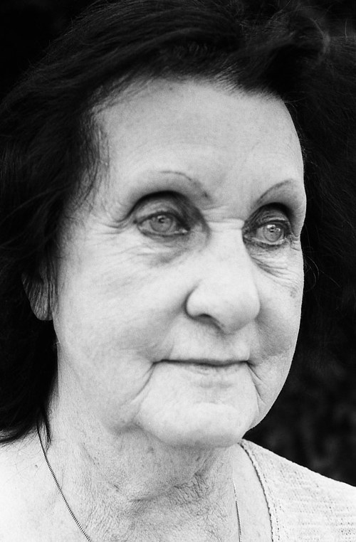 A close-up portrait of an older woman staring forward