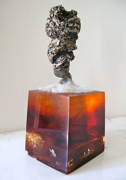 A cast bronze sculpture on a translucent orange plinth