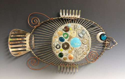 A sculpture of a fish made from varied mixed media