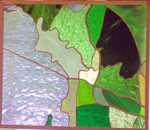 A stained glass artwork with abstract planes of green