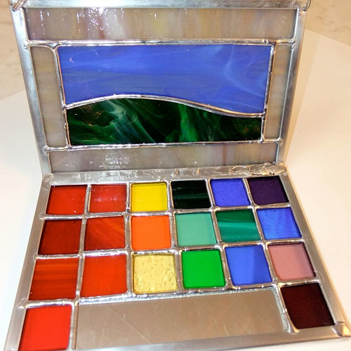 A stained glass artwork depicting a laptop or makeup palette