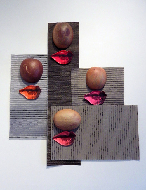 A wall-hanging artwork with abstract forms and sculpted lips
