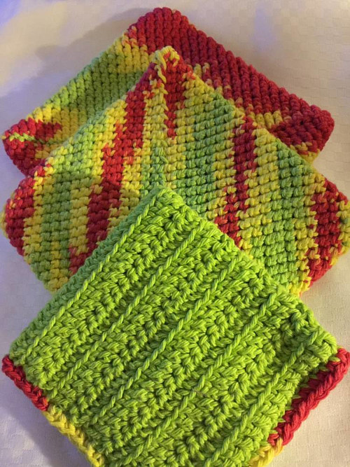 A set of hand-crocheted pot holders and dish cloths