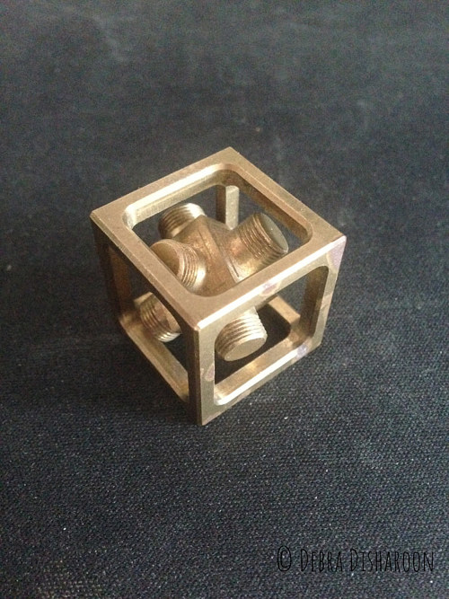 A machined brass cube