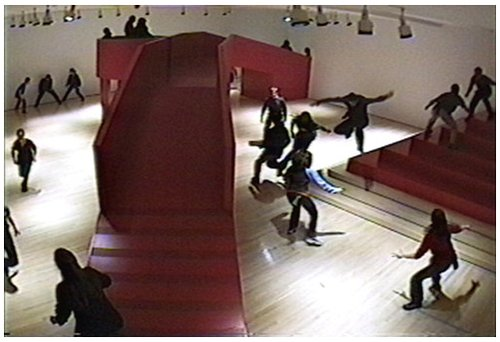 frame from a video showing red structure and people running around