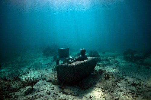 underwater photograph of a sculpture which depicts a man sitting on a couch watching tv