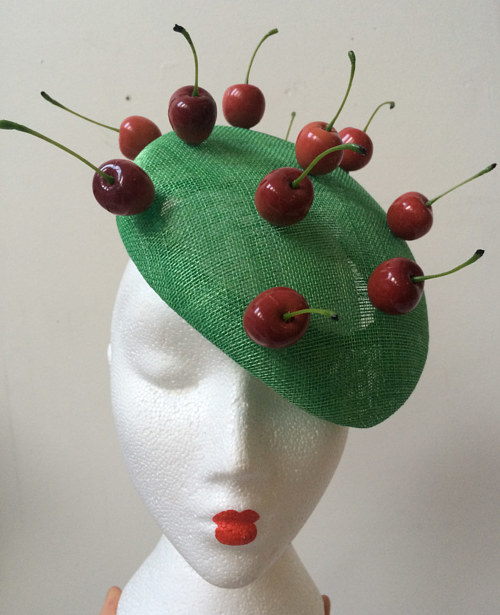 A photo of a handmade cocktail hat with cherry decorations
