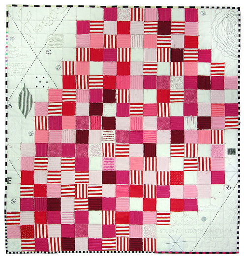 A quilt made with squares of pink on a white ground