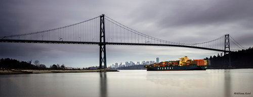 A panoramic image of a barge crossing under a bridge in Vancouver