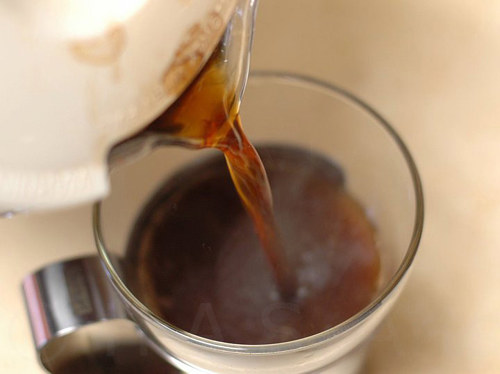 A photo of a fresh cup of coffee being poured