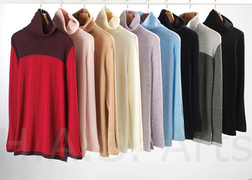 A photo of a series of sweaters on a clothing rack