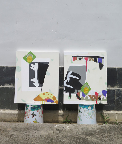 Two abstract paintings displayed on buckets