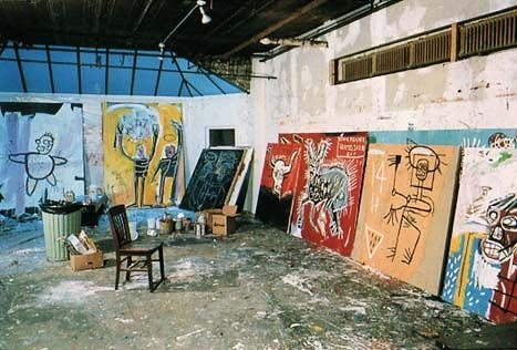 art studio of jean michel basquiat. shows empty warehouse with artworks leaning against the wall.