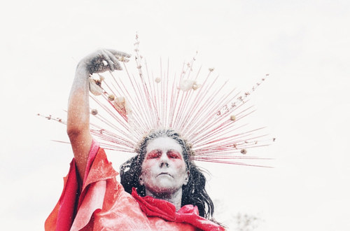A performance still of a person in an elaborate headdress