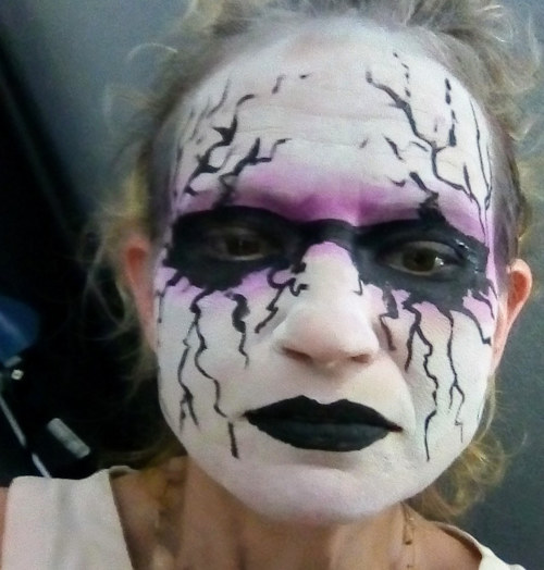 A face painting with a white ground and black streaks around the eyes