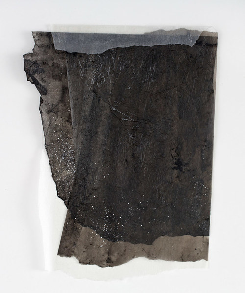 An abstract artwork with layers of dark pigment and wax