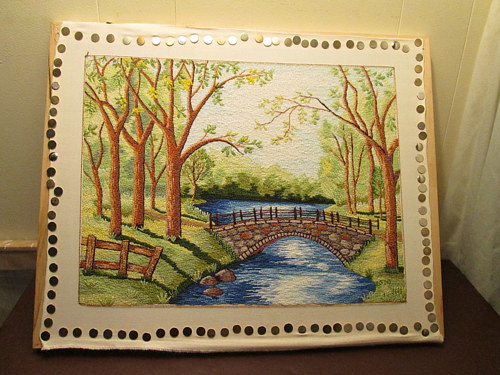 An embroidered image of a forested bridge