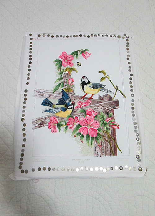 An embroidered artwork with birds and flowers