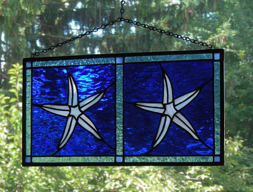 A pair of stained glass window panels with starfish