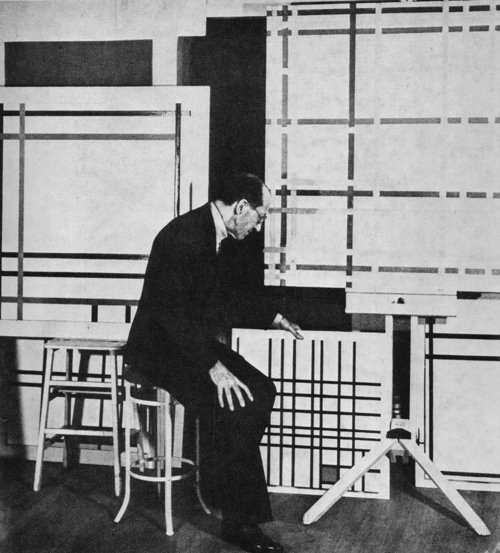 Photo of Piet Mondrian sitting on a chair in his art studio looking down towards several of his artworks