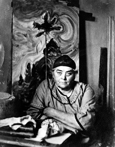 Emily Carr looking at the camera with her painting behind her