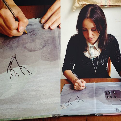 artist making a drawing inside a book