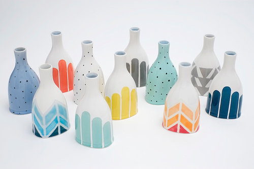 twelve ceramic sculptures shaped like bottles with color patterns on theme