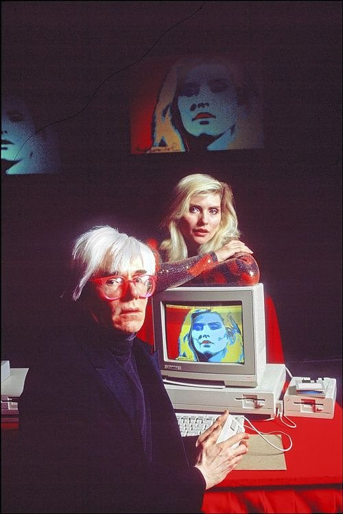 Andy Warhol using an Apple Computer with model Blondie in the background
