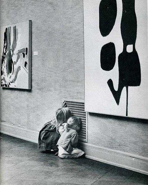 two girls look through an air vent in an art gallery