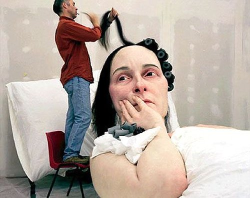 Ron Mueck putting curlers in the hair of a giant woman statue