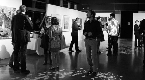 photo of art gallery reception with people standing around looking at artwork